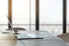 Closeup of laptop on desk top. Close up and side view of laptop and coffee cup on wooden desk top in office interior with panoramic city view and daylight. Toned stock illustration