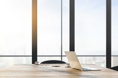Closeup of laptop on desktop. Close up and side view of laptop computer and coffee cup on wooden desktop in office interior with panoramic city view and daylight stock illustration