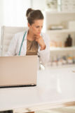 Closeup on laptop and doctor woman in background Royalty Free Stock Photos