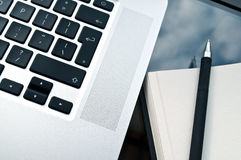 Closeup laptop keyboard with white paper. On the glass table Royalty Free Stock Photography
