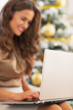 Closeup on laptop used by young woman near christmas tree Royalty Free Stock Images