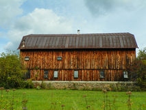 Closeup of large antique cedar wood barn with stone foundation centered in green field. Stock Photo