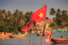 Closeup Vietnamese Flag on Fishing Boat in Sea against Palms. Closeup large red Vietnamese national flag on fishing boat in azure sea by beach against palms Stock Photos