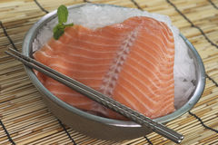Closeup of large salmon trim. In bowl full of ice with chopstick and mint leaves Royalty Free Stock Photo