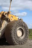 Closeup of Large yellow truck wheel protection. Such machinery is used in mining industry Royalty Free Stock Image