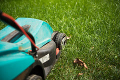Closeup lawn mower on the green grass, summertime. Cutting the lawn machine on the green grass Royalty Free Stock Photos