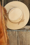 Closeup leather chaps & cowboy hat on shelf Stock Images