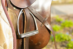 Closeup leather cowboy saddles hanging on the railing. Detail stirrup to the saddle. Removable saddles for horses in fresh air. Saddle hanging on a fence Royalty Free Stock Photography