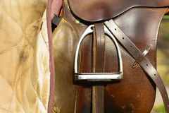 Closeup leather cowboy saddles hanging on the railing. Detail stirrup to the saddle. Removable saddles for horses in fresh air. Saddle hanging on a fence Royalty Free Stock Photo