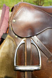 Closeup leather cowboy saddles hanging on the railing. Detail stirrup to the saddle. Removable saddles for horses in fresh air. Saddle hanging on a fence Stock Photo