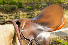 Closeup leather cowboy saddles hanging on the railing. Removable saddles for horses in fresh air. Saddle hanging on a fence stock image
