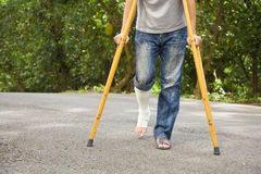 Closeup of  leg on bandage with crutches. Walking on road Royalty Free Stock Photos