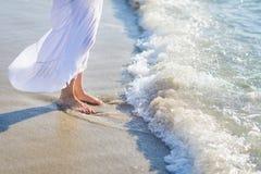 Closeup on leg of woman standing on sea shore Stock Photo