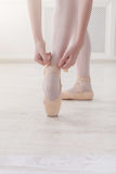 Closeup legs of ballerina puts on pointe ballet shoes Stock Photos
