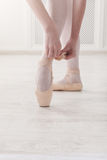 Closeup legs of ballerina puts on pointe ballet shoes royalty free stock images