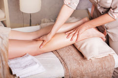 Closeup of legs, Caucasian woman having a massage spa salon. Woman having  therapeutic leg massage in spa salon, closeup Royalty Free Stock Images