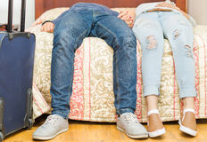 Closeup legs couple wearing jeans, sitting on edge of bed, blue suitcase standing beside, hostel concept Stock Images