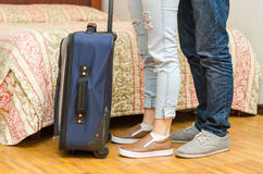 Closeup legs of couple wearing jeans, standing next to bed, blue suitcase on floor, hostel concept Stock Photos