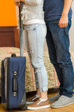 Closeup legs of couple wearing jeans, standing next to bed, blue suitcase on floor, hostel concept Stock Photography