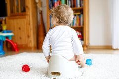 Closeup of legs of cute little 12 months old toddler baby girl child sitting on potty. Kid playing with educational toy and Toilet training concept. Baby stock image