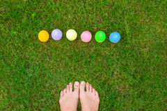 Closeup of legs and Easter eggs on green grass Stock Image