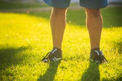Legs of Man on Sunny Green Grass Lawn. Closeup legs of european old man doing morning exercises on sunny green grass lawn in park Royalty Free Stock Image