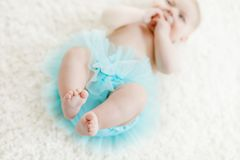 Closeup of legs and feet of baby girl on white background wearing turquoise tutu skirt. Cute little child laughing and smiling. Happy carefree baby. Childhood Stock Photos