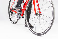 Closeup of Legs of Female Cyclist and Wheels of the Road Bike Placed in Studio. Royalty Free Stock Photos