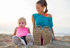 Closeup on legs of fitness mother and baby girl Royalty Free Stock Images