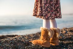 Closeup of legs little girl in cozy fur boots Royalty Free Stock Photography