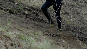 Closeup of legs of runners going uphill stock video footage