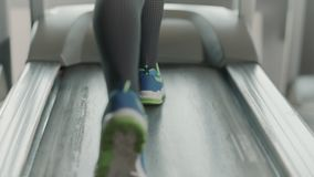Closeup legs running on treadmill in fitness gym. Back view of fitness shoes. Walking on treadmill. Close up feet training in sport club in slow motion stock video