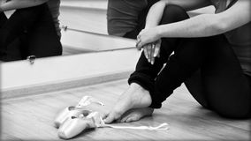 Closeup on legs and shoes. A ballerina taking off the ballet shoes sitting on the floor in the studio Stock Image