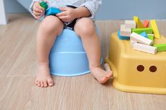 Closeup of legs of toddler boy sitting on potty. Closeup of legs of cute little Asian 18 months old toddler baby boy child sitting on potty playing with wooden stock images