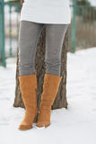 Closeup on legs of woman leaning against tree in winter park Royalty Free Stock Photo