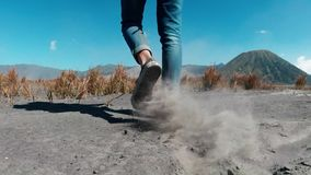 Closeup legs of woman walking in a volcanic dusty desert near beautiful Mount Bromo in East Java. Indonesia - video in slow motion stock footage