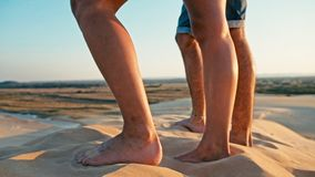 closeup of the legs of a young woman and man enjoying the sunset on the peak of one of the desert sand dune stock image