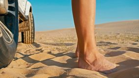 closeup of the legs of a young woman next to a 4x4 car vehicle enjoying the sunset on one of the desert sand dune royalty free stock image
