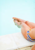 Closeup on legs of young woman sitting near pool Stock Photos