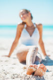 Closeup on legs of young woman in swimsuit sitting on beach Stock Image