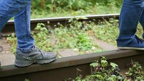 closeup Les jambes sont sur des voies de train Le type marchant sur le chemin de fer clips vidéos