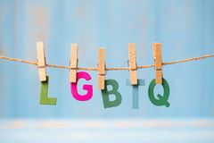 Closeup LGBTQ text, for lesbian, gay, bisexual, transgender, and hanging on line with blue wooden background. Closeup LGBTQ text, for lesbian, gay, bisexual stock photography