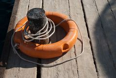 Close up of lifebuoy. Rescue equipment for emergency on water. Lifebuoy and mooring cannon on dock royalty free stock photo