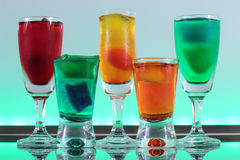 Closeup of a line of colorful cocktails resting on the bar with led lighting at a club Stock Photo
