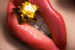 Closeup lips with fashion red make-up & christmas gold lucky star Royalty Free Stock Images