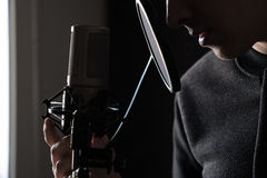Closeup of lips and hands on a microphone of a young man standing in profile. Horizontal photo Stock Photos