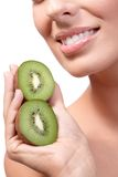 Closeup lips of smiling woman with kiwi Stock Photography