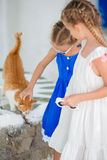 Closeup of Little adorable girls stroking a red cat in greek village, Mykonos, Greece, Europe Royalty Free Stock Images