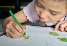 Closeup little asian girl hand draw her picture with color penci Stock Photo