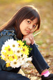 Closeup little asian girl holding flowers Royalty Free Stock Photos